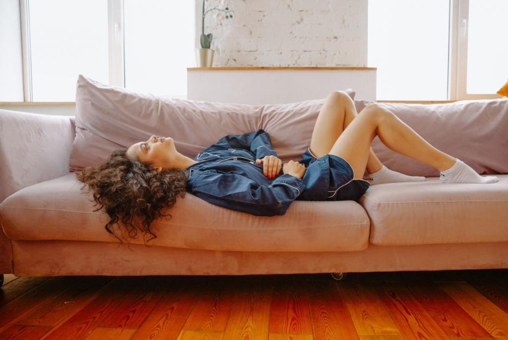 Imagem de mulher deitada no sofá aparentando estar com cólica.