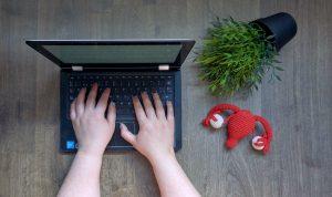 imagem vista de cima de mãos femininas fazendo uma pesquisa sobre alteração na espessura do endométrio em um notebook. Ao lado, apoiada na mesa, um utero de crochê e uma planta.