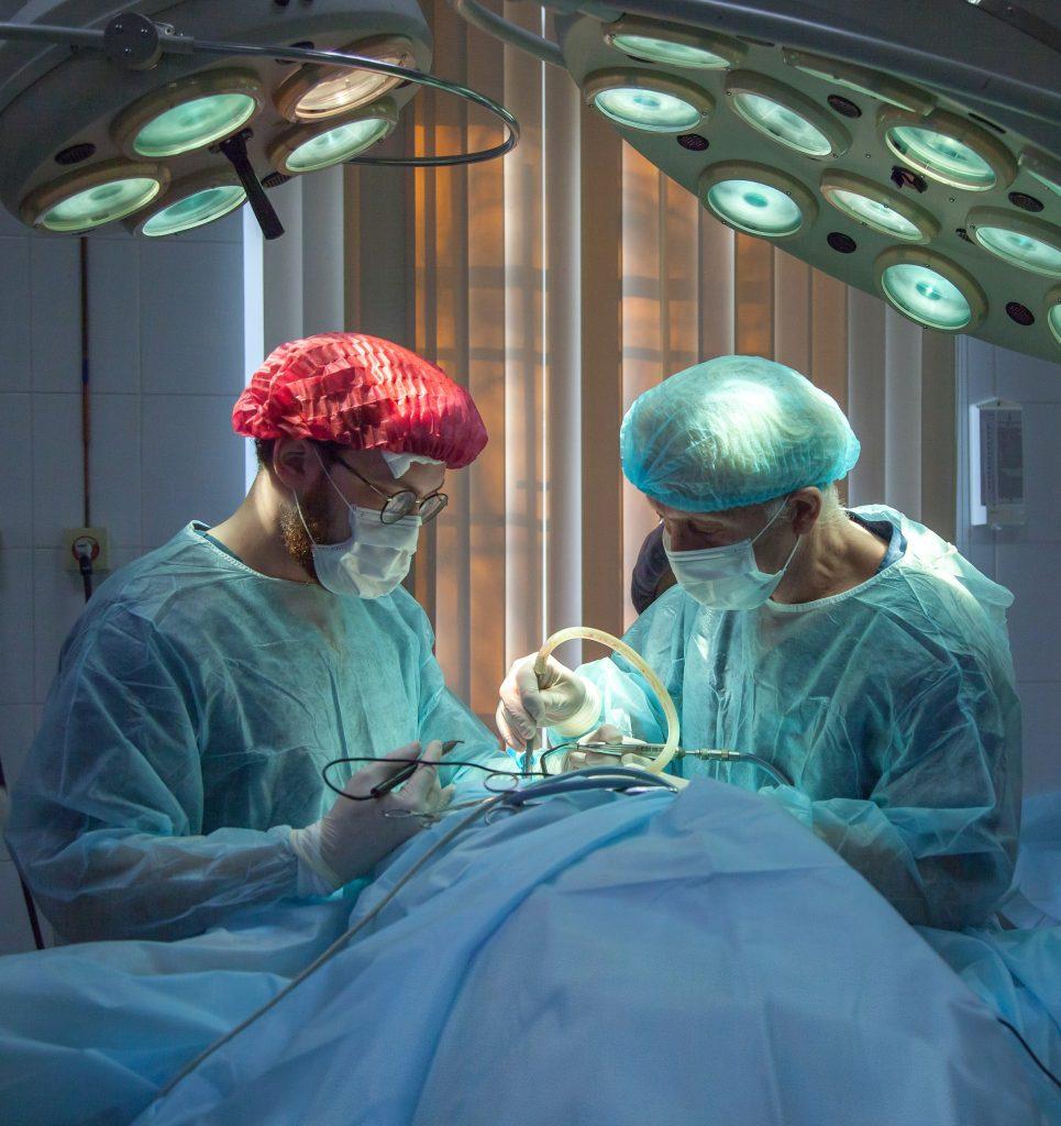 Na imagem, podemos ver uma mesa de cirurgia com dois médicos
